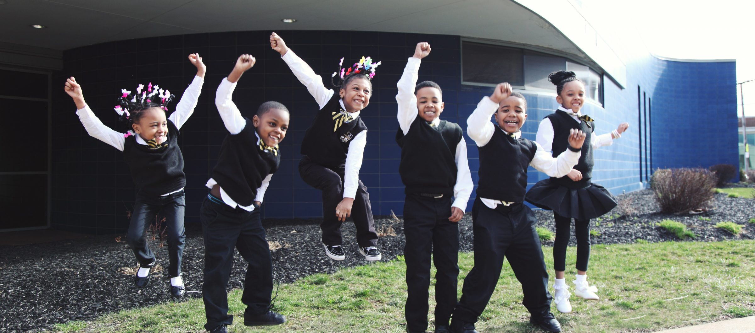 Young elementary students in uniform jumping and smiling outside.