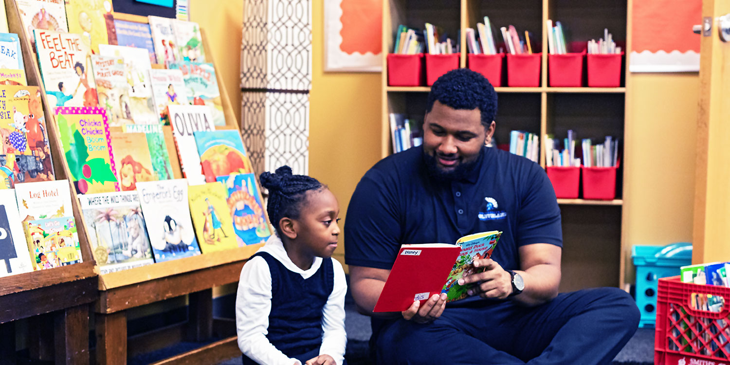 Teacher reading a book to an elementary student.