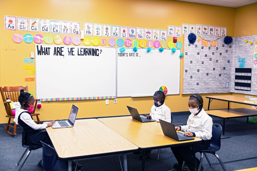 Elementary students sitting at desks with headphones and laptops.