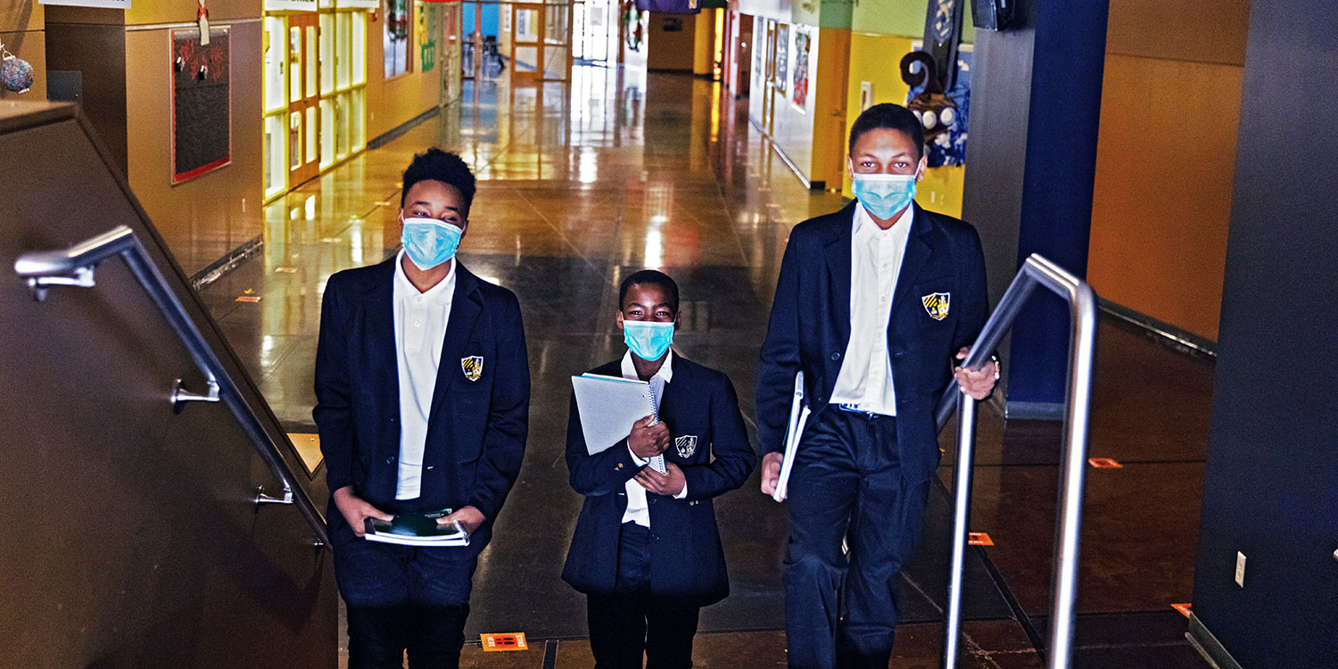 Three middle school students walking up stairs in hallway.