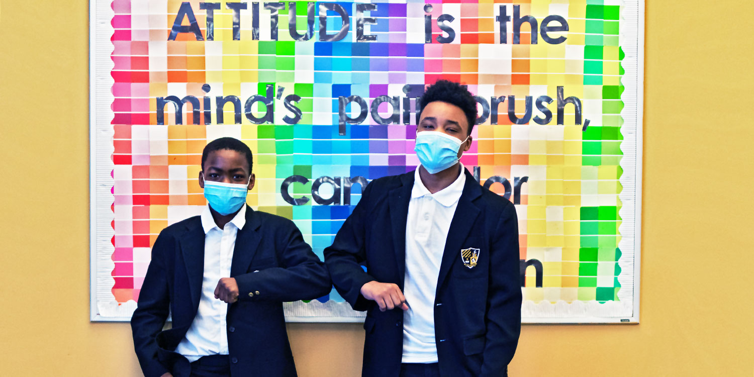 Two masked students in front of a hallway bulletin board touching elbows.