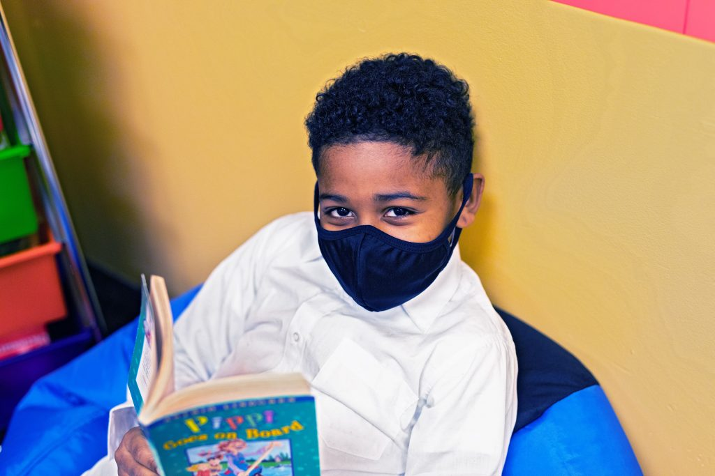 Elementary student sitting in beanbag and reading a book.